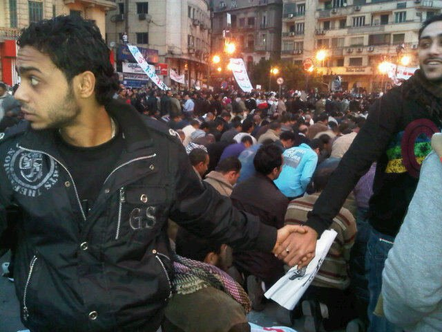 Christians protecting Muslims while they pray during protests in Egypt.