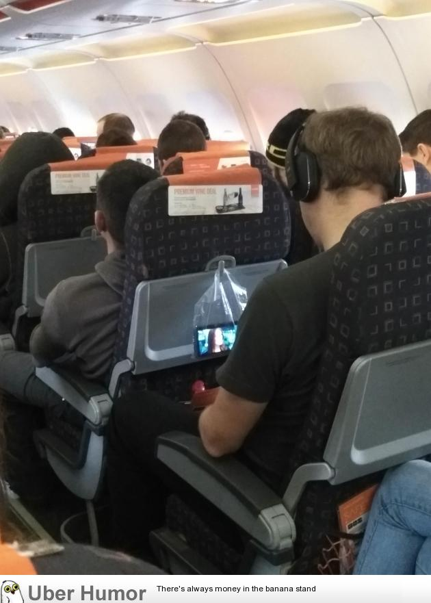 This genius watching Taken using a clear plastic bag to hold his phone on a plane.   uberHumor.com